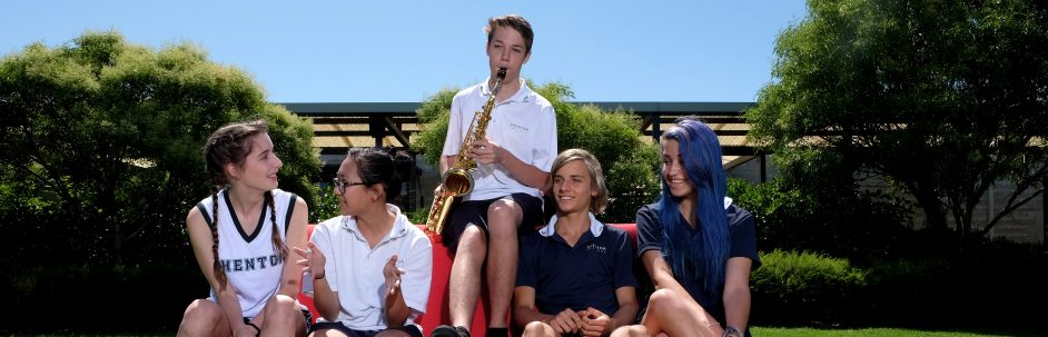 Five students sitting on red couch under blue sky, one playing saxophone