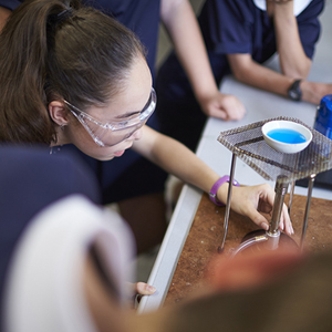 female student in a lab heating small bowl with blue liquid with a bunsen burner