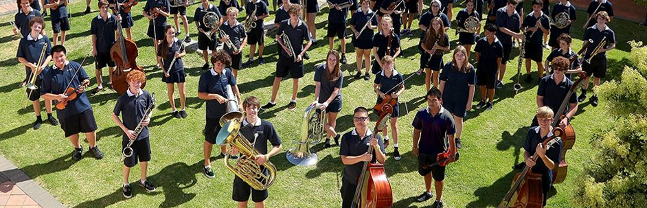 big group of students on lawn, each holding their instrument