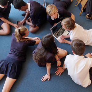 Group of students laying on their bellies on the floor looking at a laptop