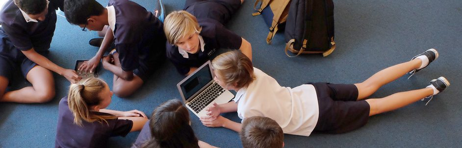 students laying on their bellies on the floor looking at a laptop