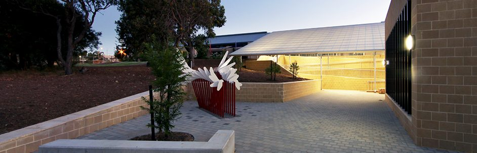 abstract sculpture with white wings in front of a school building