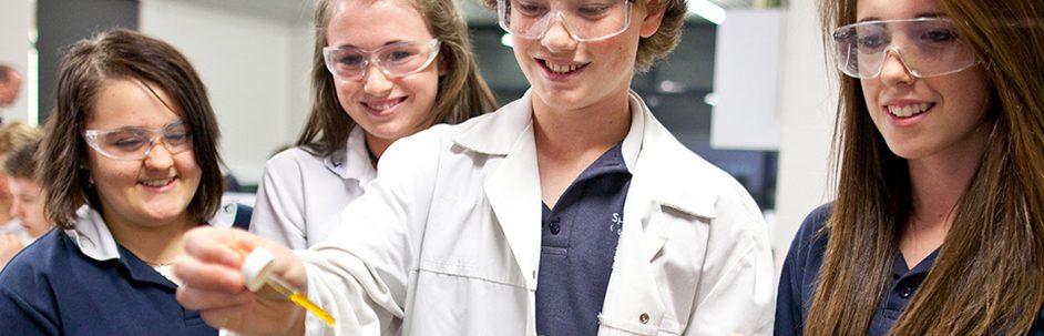 Four girls wearing safety glasses and lab coats, one holding a pipette with a yellow liquid