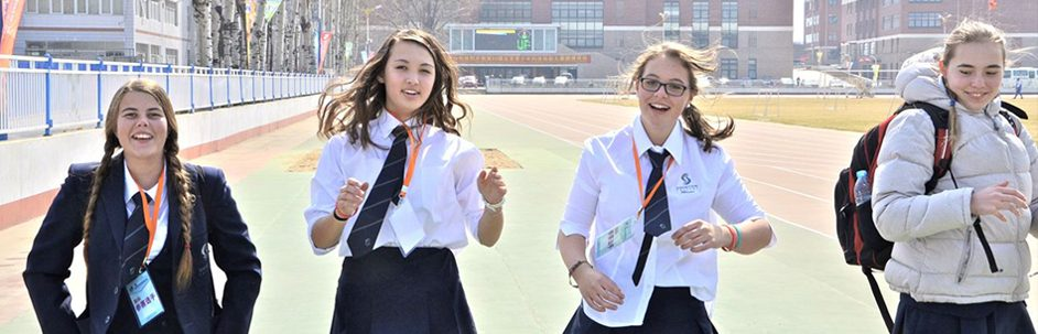 Four girls outdoors in a city wearing formal school uniform