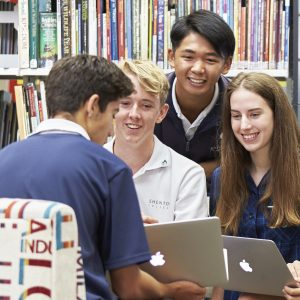 Group of students in the library looking at a laptop