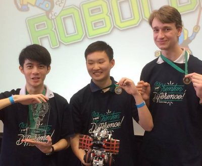 three students holding up medals and a trophy