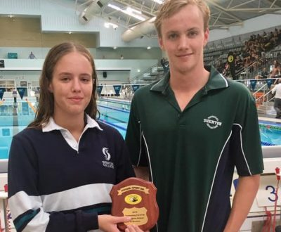 A boy and a girl with wet hair in front of a swimming pool holding a trophy