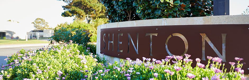 Shenton College entrance sign with flowers and trees