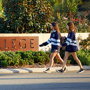Two female students walking past the Shenton College entrance sign