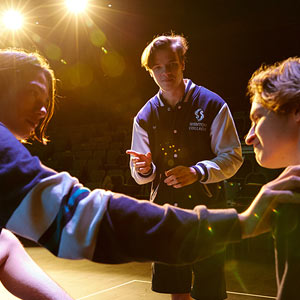 Students on a stage rehearsing a dramatic performance