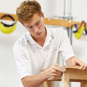 Male student wearing safety glasses and sanding a woodworking project