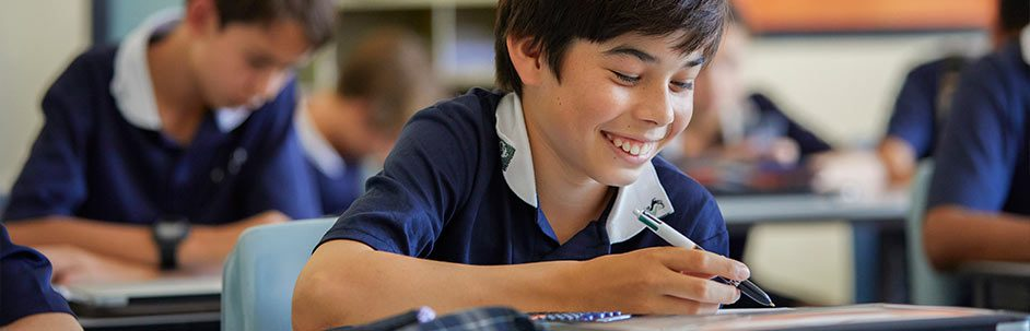 Male student sitting at a desk while smiling and writing in an exercise book