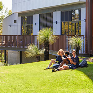A group of students sitting on a sloping lawn with a building exterior behind them and bushland in front of them