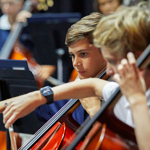 Two male students playing cello in school orchestra