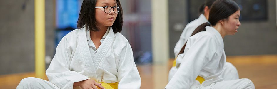 Female students practicing moves in martial arts uniform