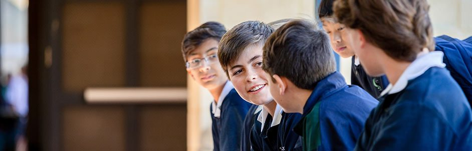 Group of male students talking and smiling while sitting on a bench outside