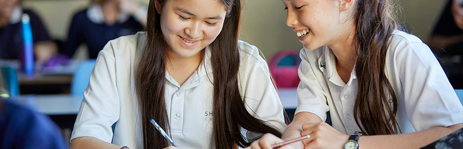 Two female students writing in a workbook and smiling in a classroom