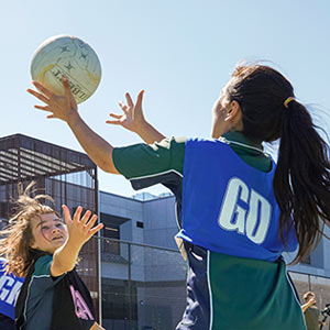 Female student in netball bib catching a netball during an outdoor game