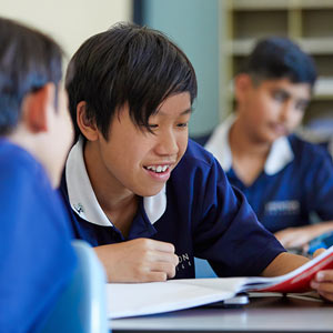 Male student showing exercise book to classmate in classroom