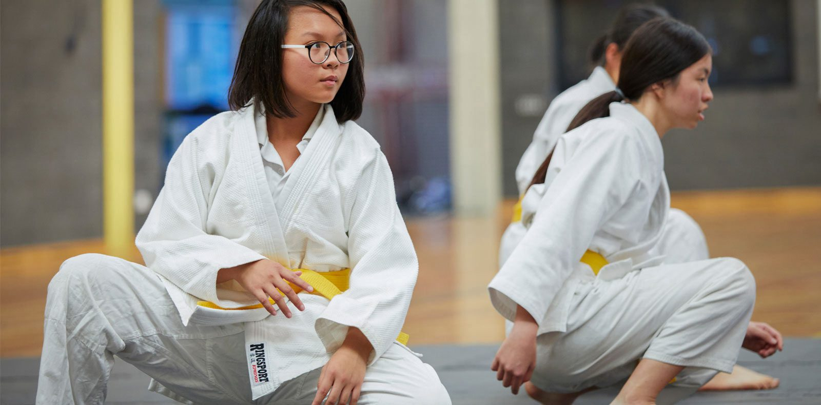 Female student practicing a move in martial arts uniform