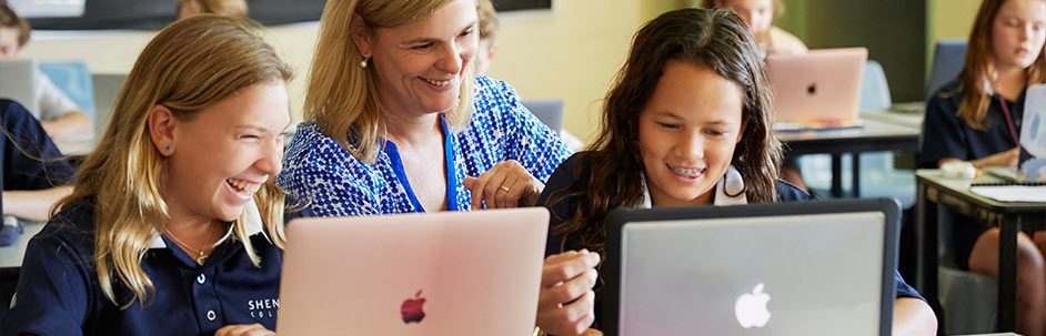 Female teacher and two female students laughing while looking at laptop screens
