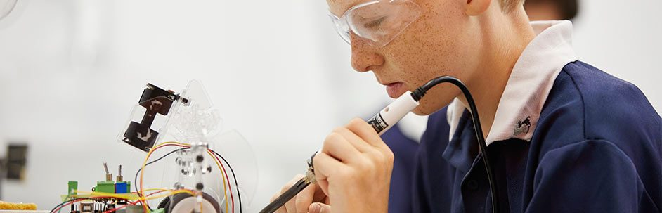 Closeup of male student wearing safety glasses and using a soldering iron