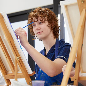 Male student in art class painting on a canvas on an easel with classmates in background