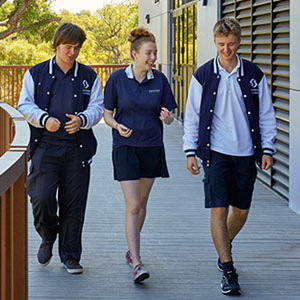 Four students walking and laughing on an exterior walkway with trees and students in the background