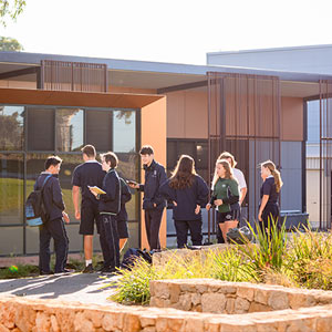 Exterior view of school building with a group of Upper Senior students outside