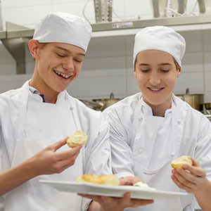 Vocational program students wearing chef uniforms and holding up scones