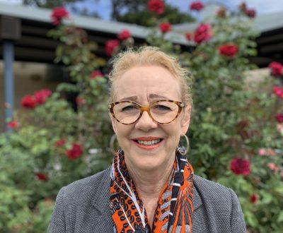 Meredith Eddington standing in front of the rosebush